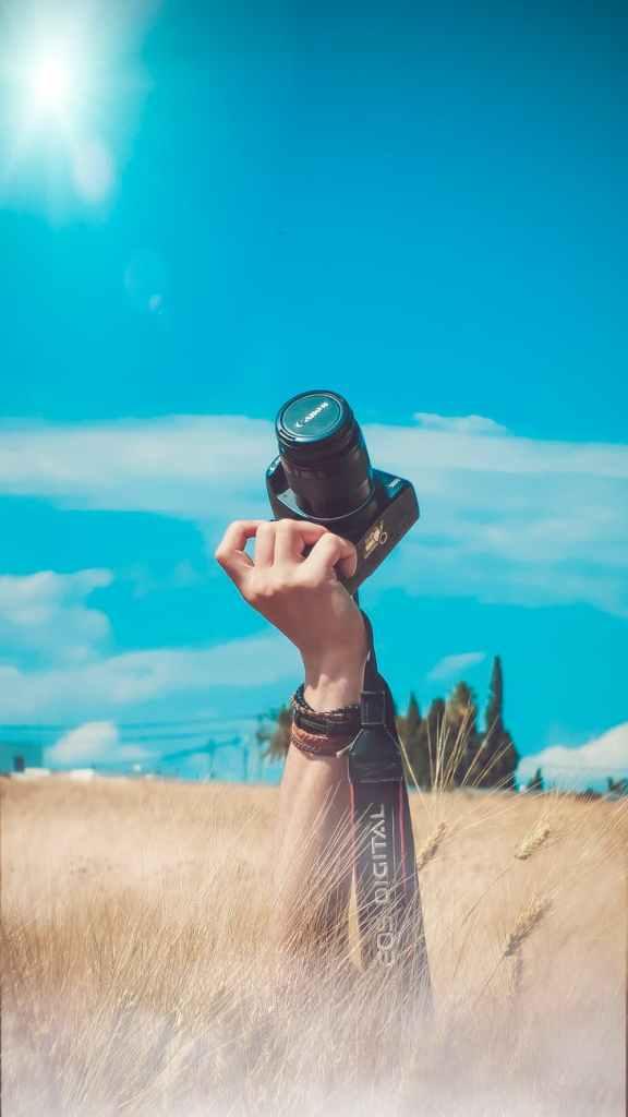 person holding black canon dslr camera kit